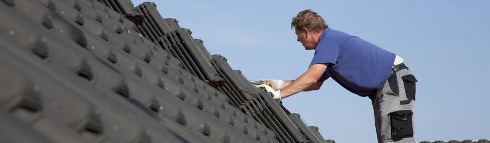 dakdekker werkt op een dakpannen dak